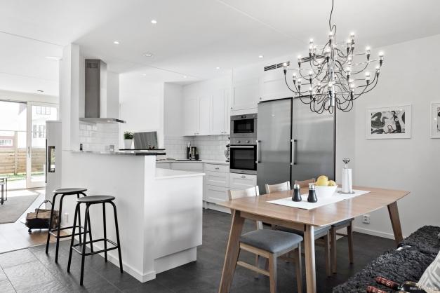 Köket är i vitt och från Ballingslöv med vita bänkskivor. Kyl och frys samt häll, ugn, micro och diskmaskin. Stilrent och snyggt! Bardisken har en stenskiva i mörkt grått