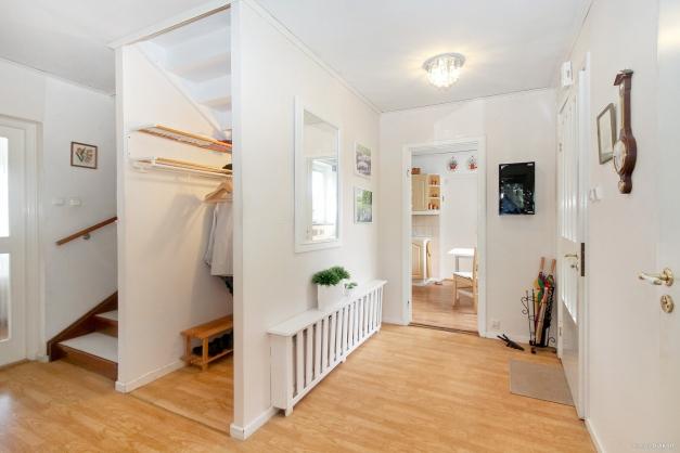 Välkomnande hall med kapprum och toalett samt trappa till ovanvåning