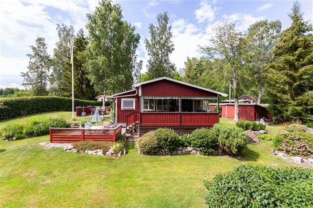 Fritidshuset har en stor inglasad altan och uteplats med utsikt över sjön.