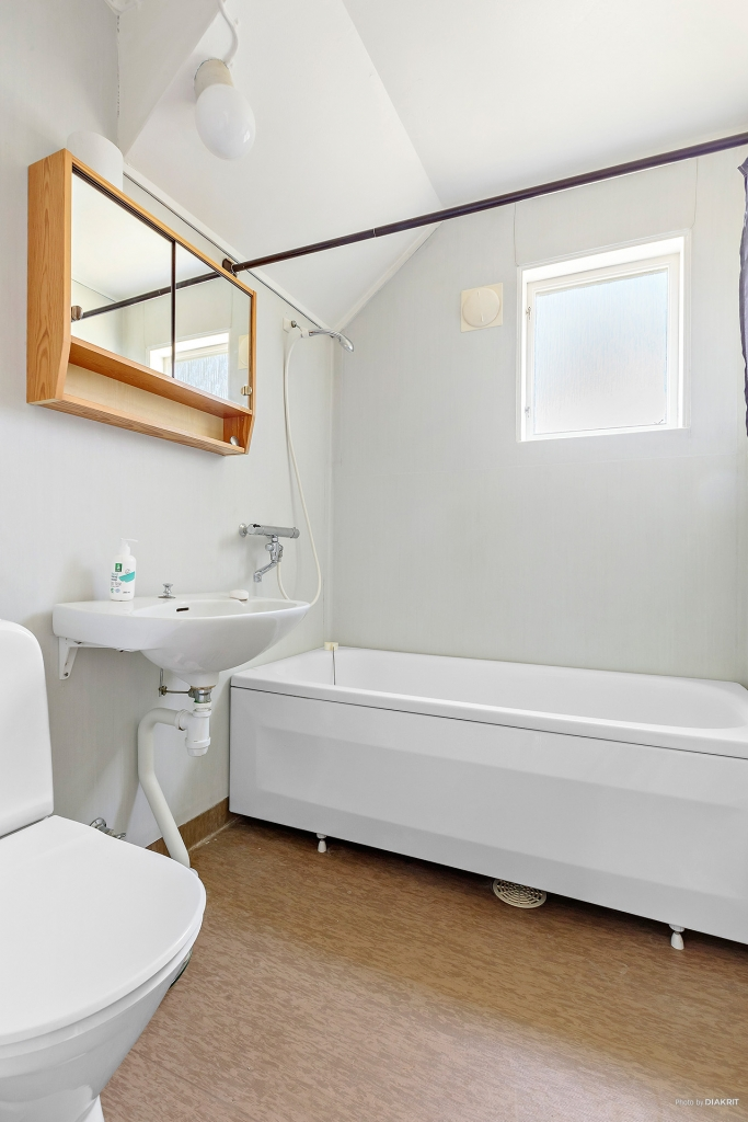 Badrum med badkar, wc, tvättställ och torkgarderob