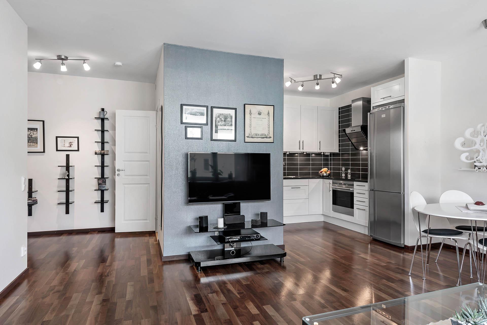 Öppen planlösning mellan kök och vardagsrum, perfekt placering av TV:n i mitten