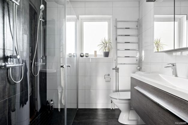 Helkaklat badrum med stora fina plattor på både golv och vägg. Smidigt med dubbla duschar.