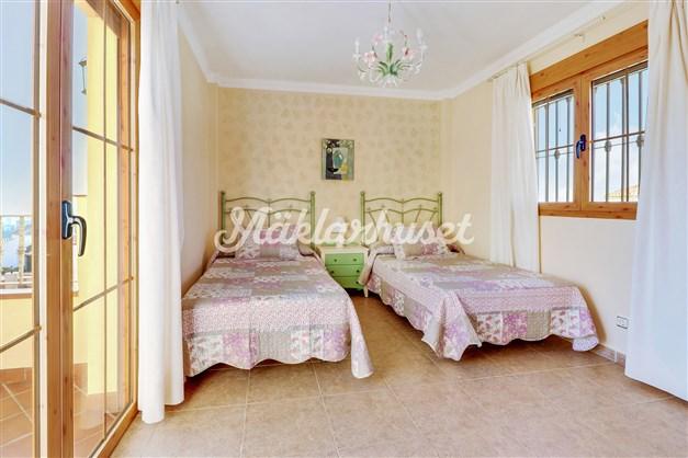 Sovrum med garderobsvägg och utgång till stor balkong