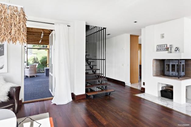 Allrum mellanvåning med kamin och utgång till balkong.