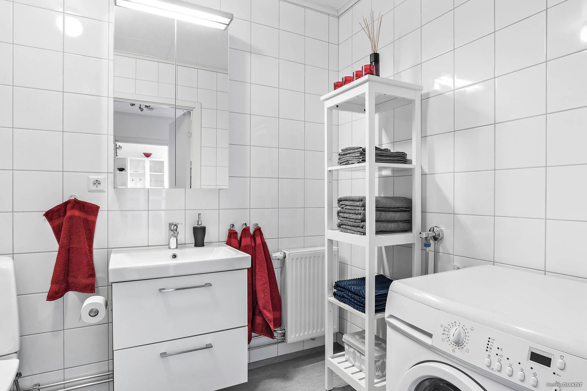 Stort duschrum med tvättmaskin och plats för hylla