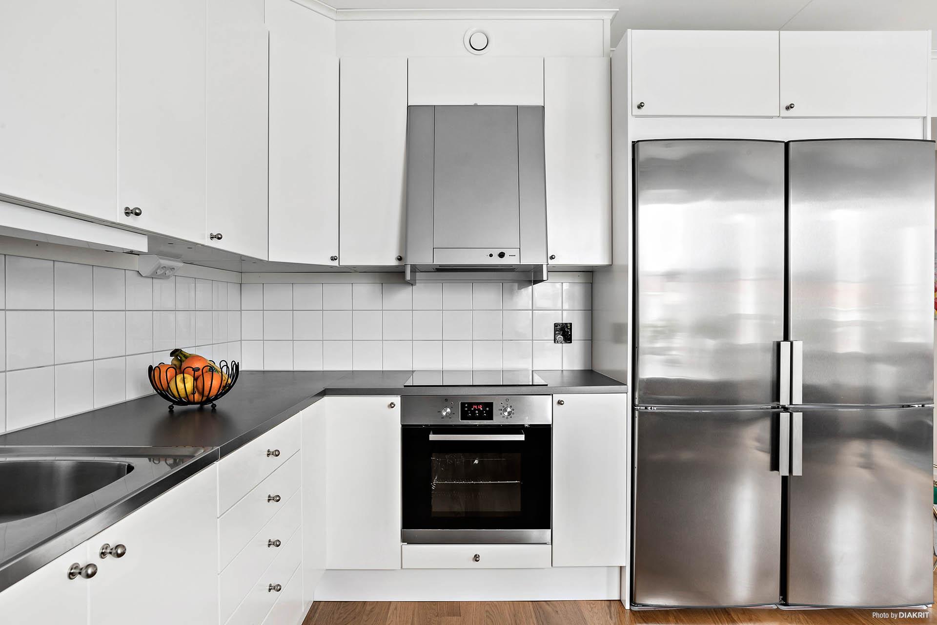 Stilrent kök med vita snickerier och rostfria vitvaror