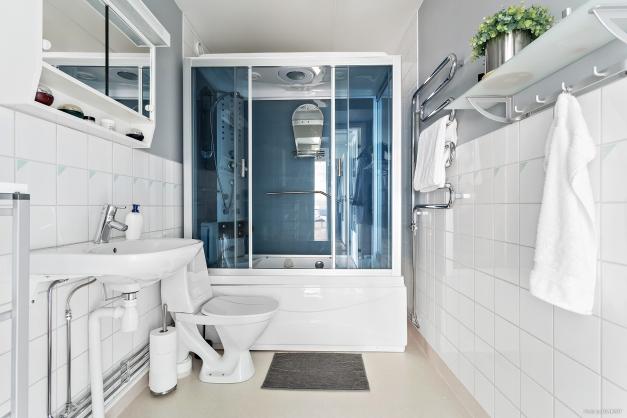 Badrum med badkar med ångbastu.