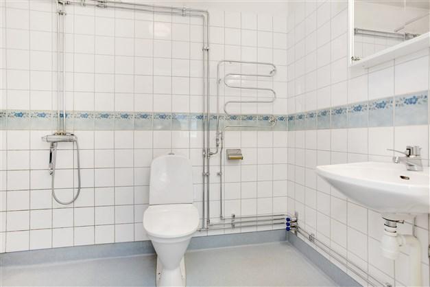 Dusch/wc med kakel på vägg och plastmatta på golv. Här är förberett för tvättmaskin, för den som önskar.