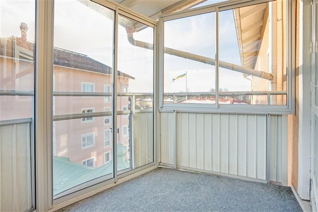 Balkongen har terassmatta, skjutglas och skjutdörrar.