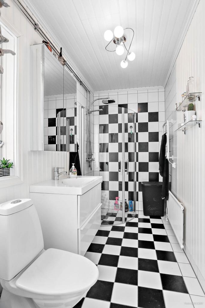 Lägenhet 2: Toalett/dusch med kakel och klinker samt träpanel