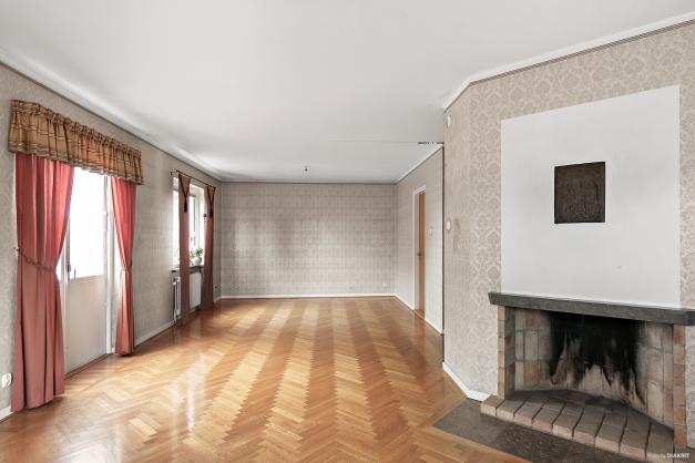Lägenhet övre plan.  Vardagsrum med stavparkett och öppenspis (ur funktion)