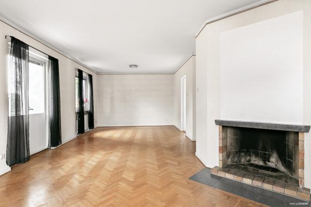 Lägenhet på bottenplan.  Vardagsrum i fil med stavparkett och öppenspis (ur funktion).