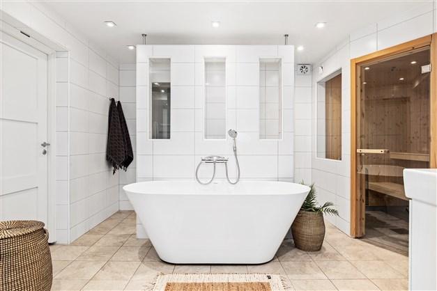 Badrum med bastu, badkar och dubbla duschar