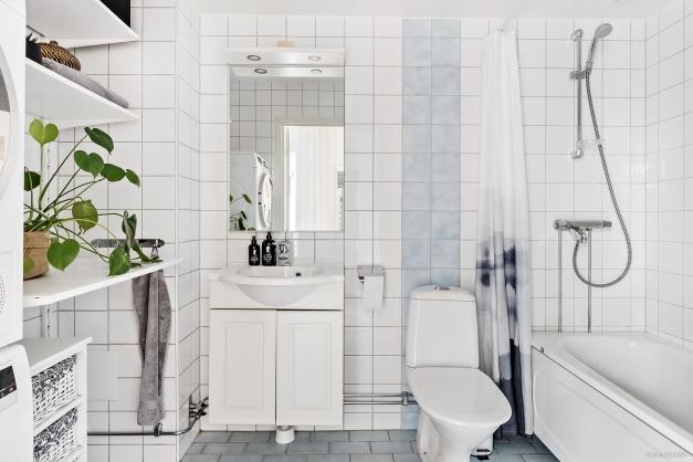 Helkaklat badrum med båda tvättmaskin och torktumlare.