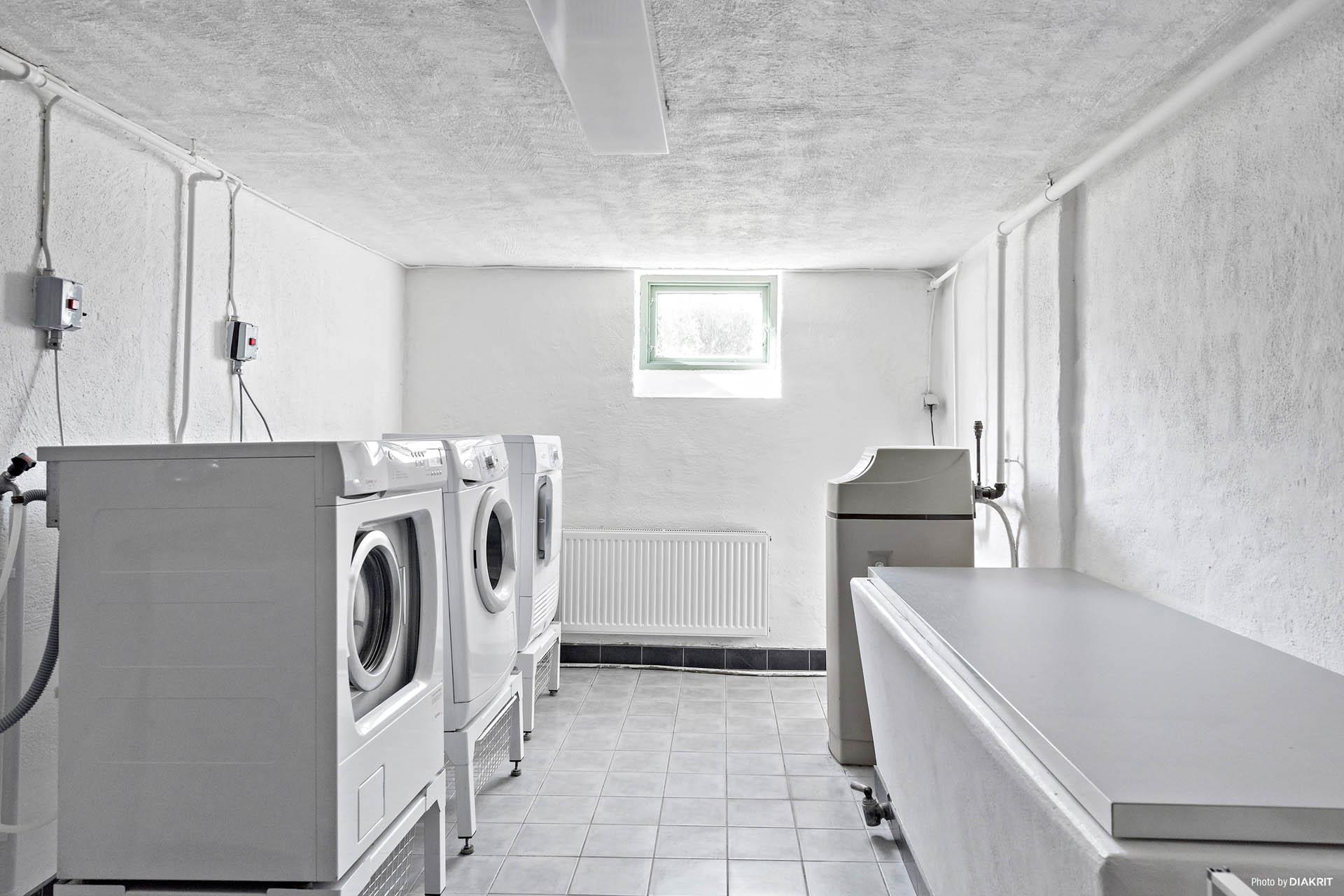 Modern och välutrustad tvättstuga på källarplan. Tvättmaskiner, torktumlare och torkrum finns att tillgå. På det gamla tvättkaret finns plats att stå och vika tvätt.