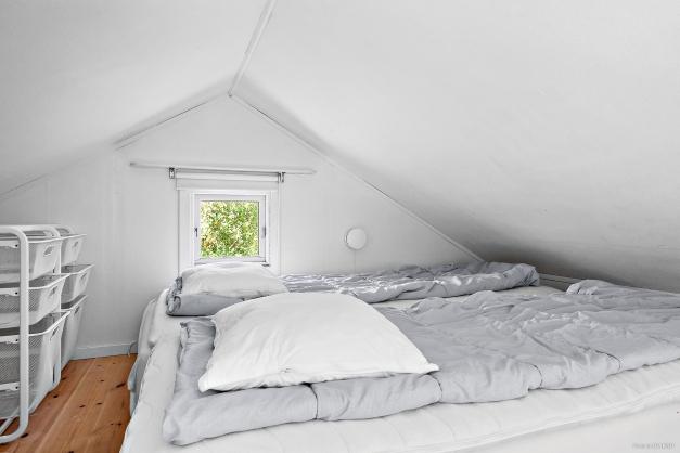 Mysigt sovloft med plats för stor madrass samt förvaring.