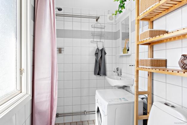 Helkaklat och fräsch badrum inrett med dusch och tvättmaskin.