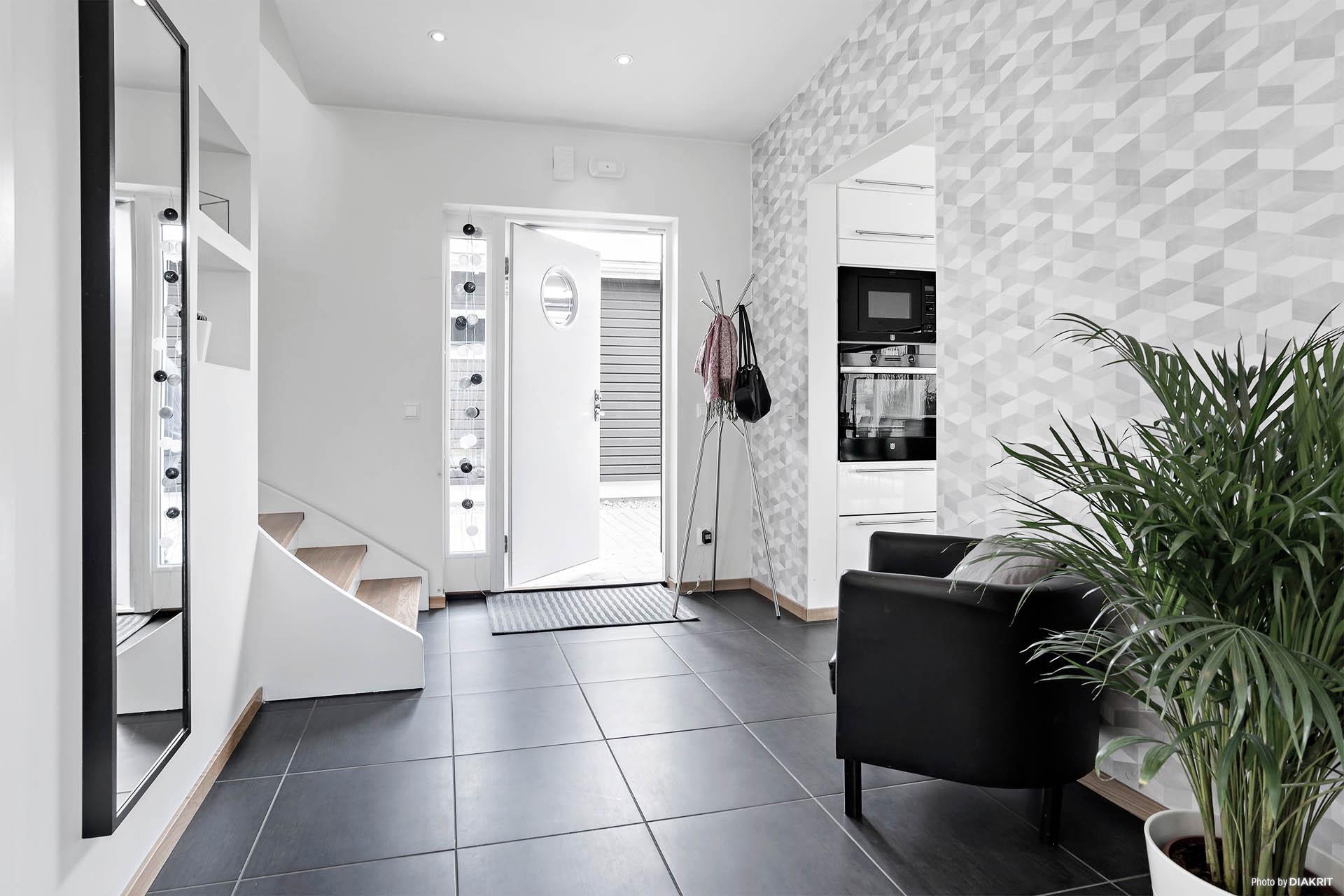 Rymlig hall med klinkers och tapeter med modern design.