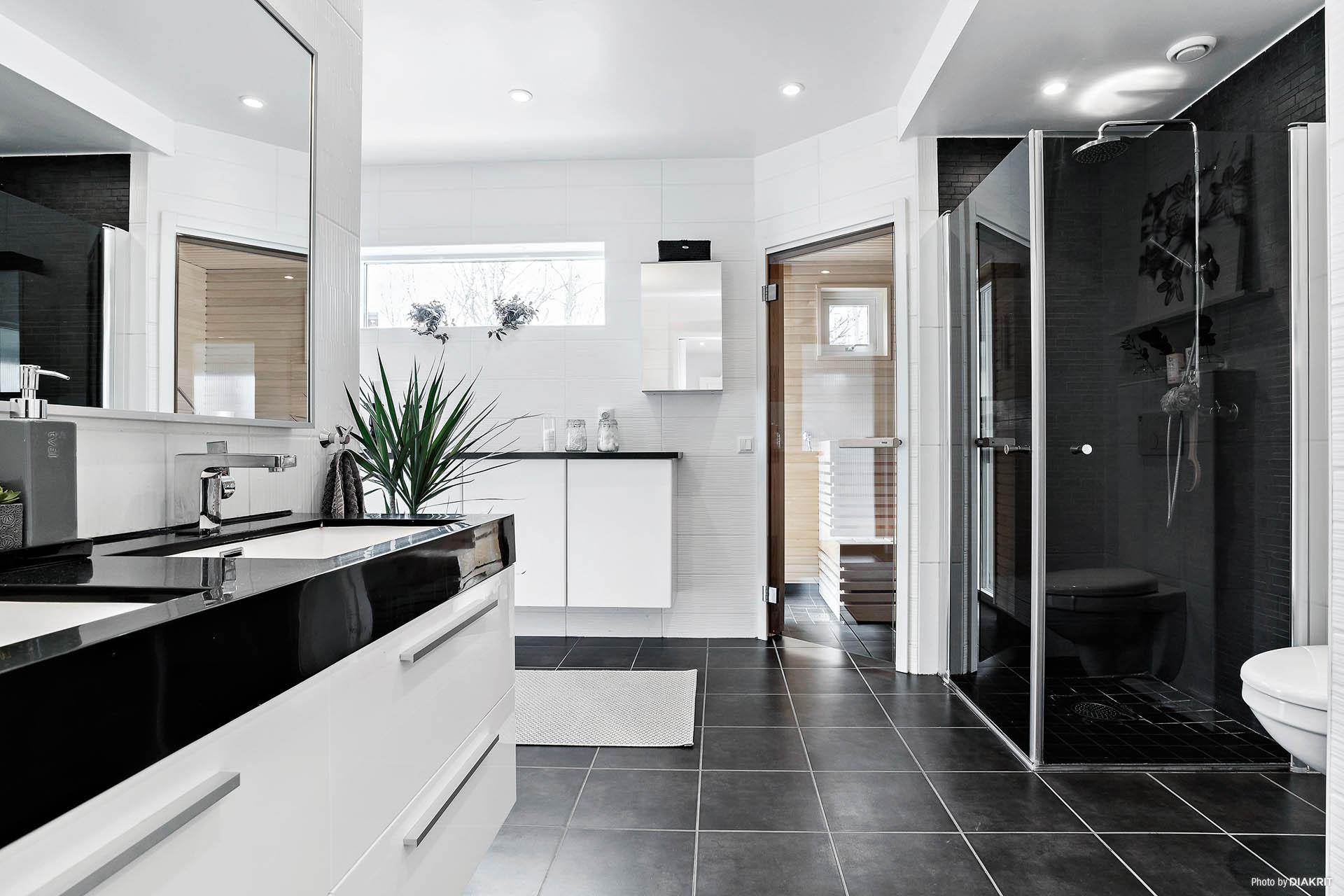 Helkaklat bad- och duschrum med bastu och bubbelbadkar.