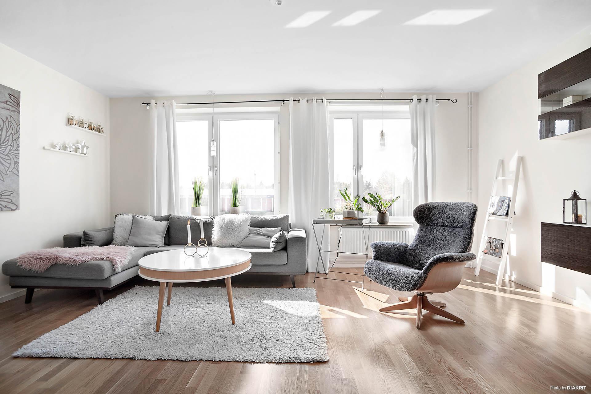 Ljust vardagsrum med stora fönster