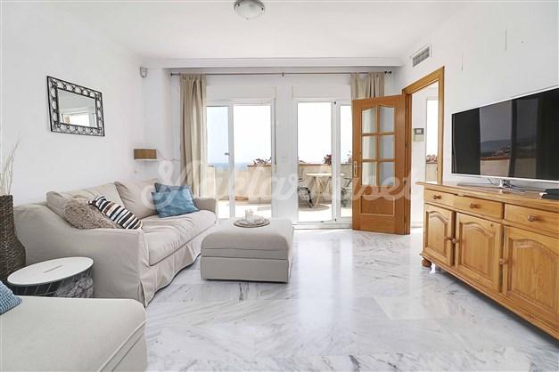 Vardagsrummet har stora fönsterpartier med havsutsikt och utgång till terrassen