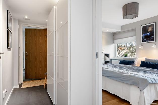 Entrén med lampspotar i taket och anslutning till sovrum 1.