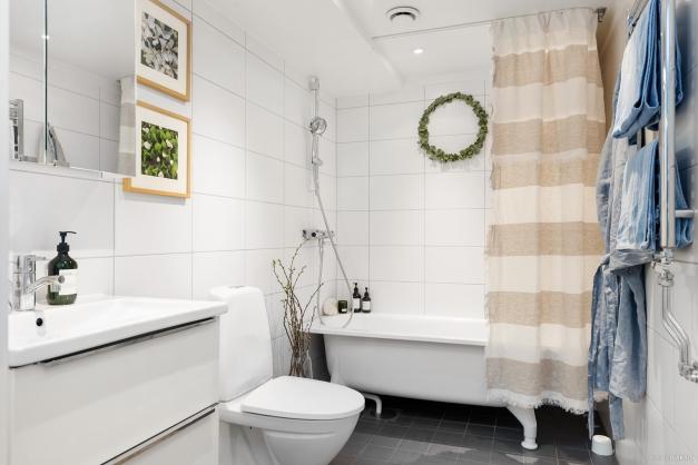 Nyrenoverat och fräscht badrum i svart och vitt.