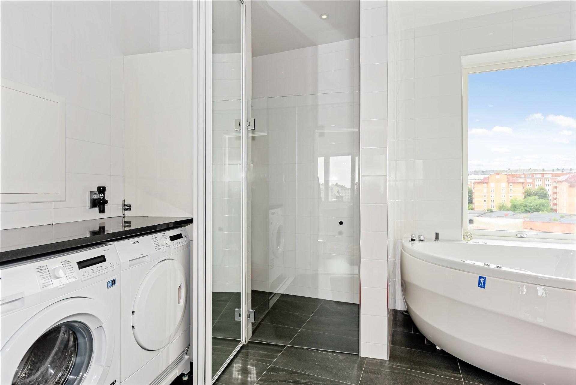 Bakom skjutdörrsgarderoben finns tvättmaskin, torktumlare och plats för förvaring