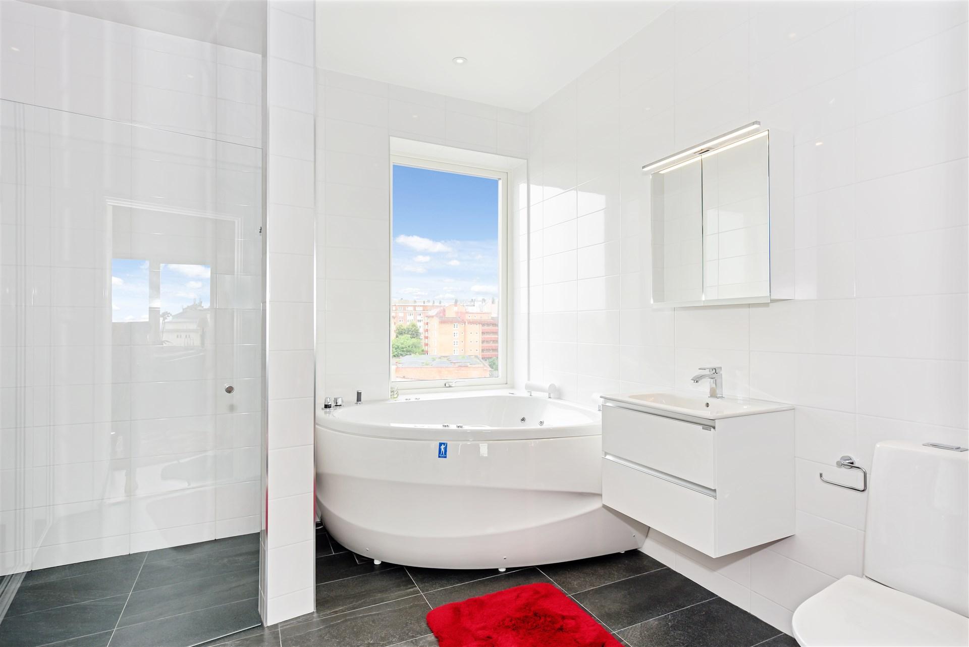 Badrum med bubbelbadkar, dusch, tvättmaskin och torktumlare
