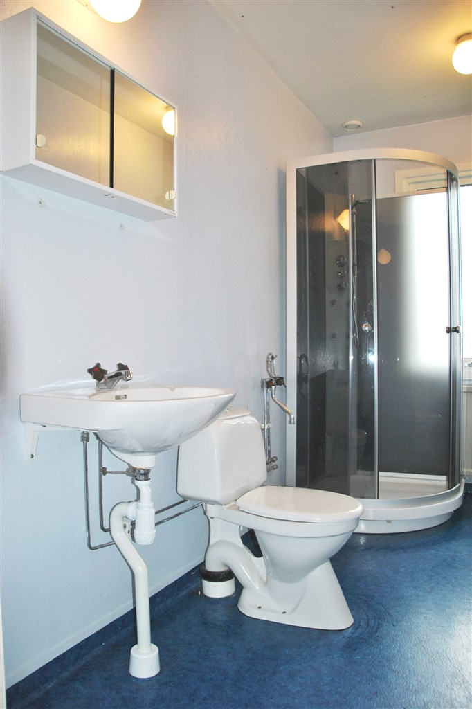 Badrum med duschkabin och fönster.