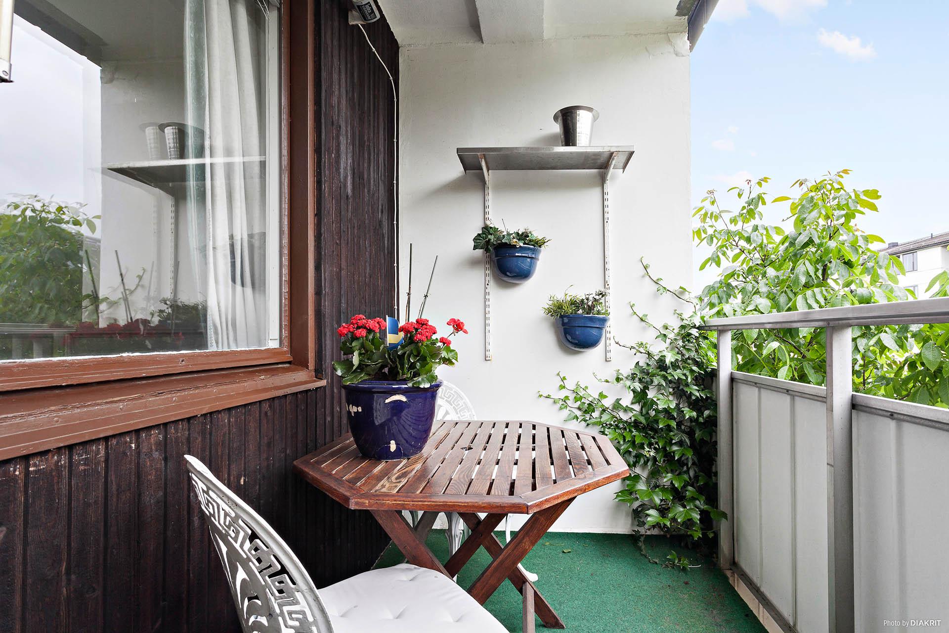 Mysig balkong omringad av mycket grönska.