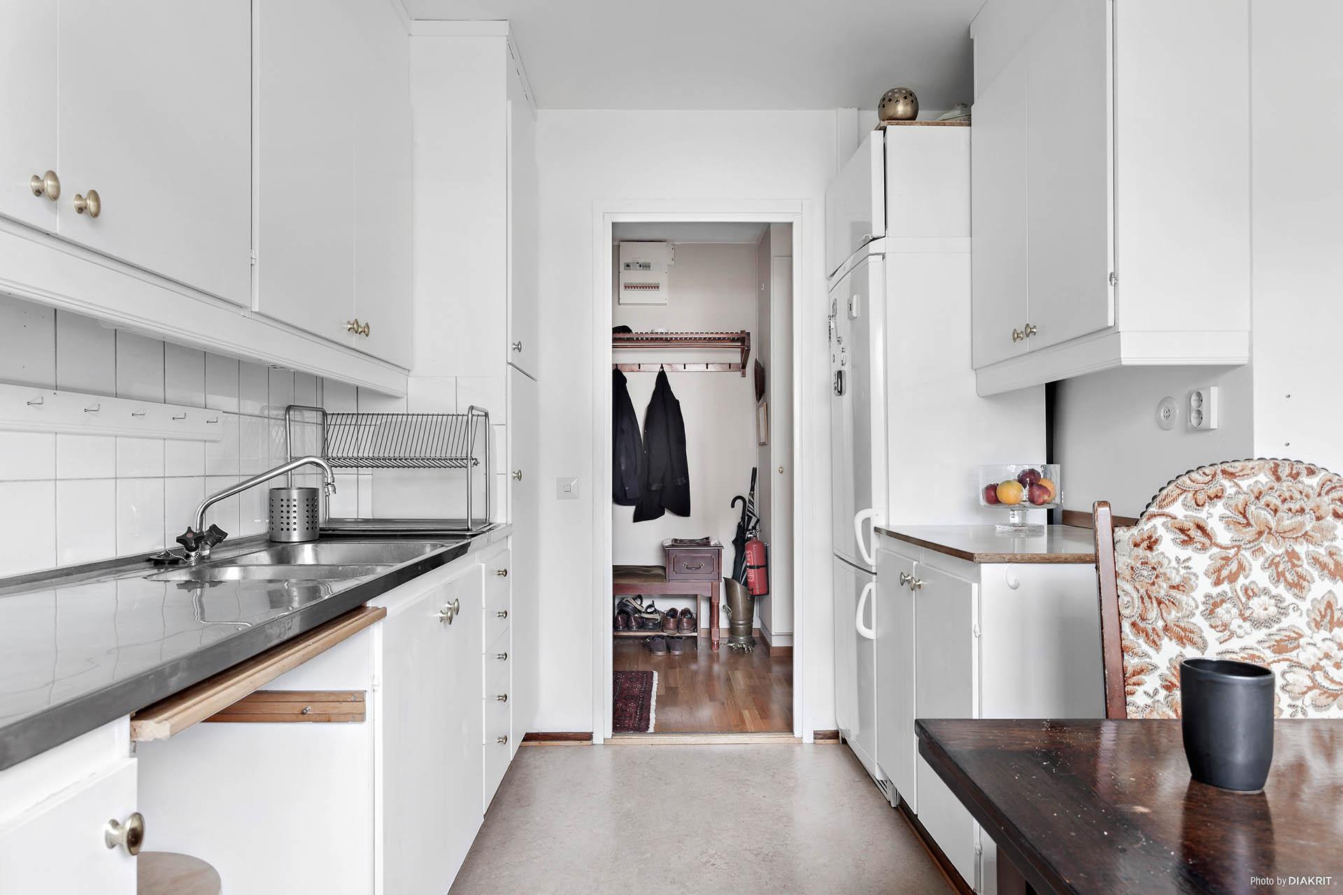 Ljust & vitt kök med gott om skåpluckor och plats för större matbord.