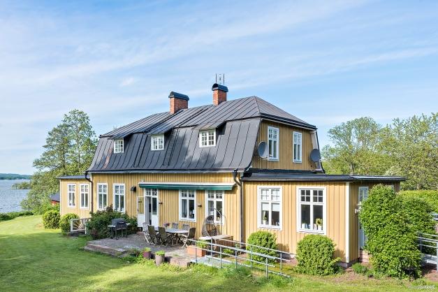 Villan är charmerande i sin stil och utsikten över sjön är närvarande från alla håll på tomten. Här ser vi uteplatsen och trädgårdssidan