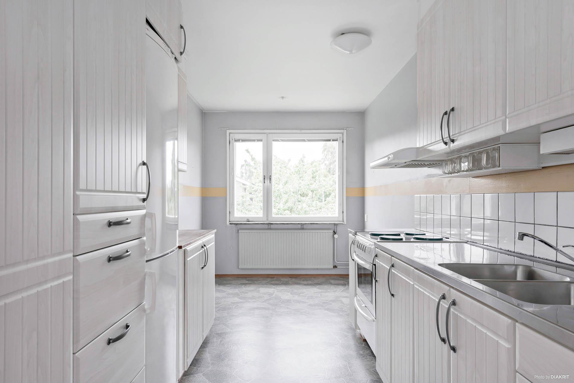 Arbetsvänligt kök med vita fräscha luckor och gott om plats för matplats.
