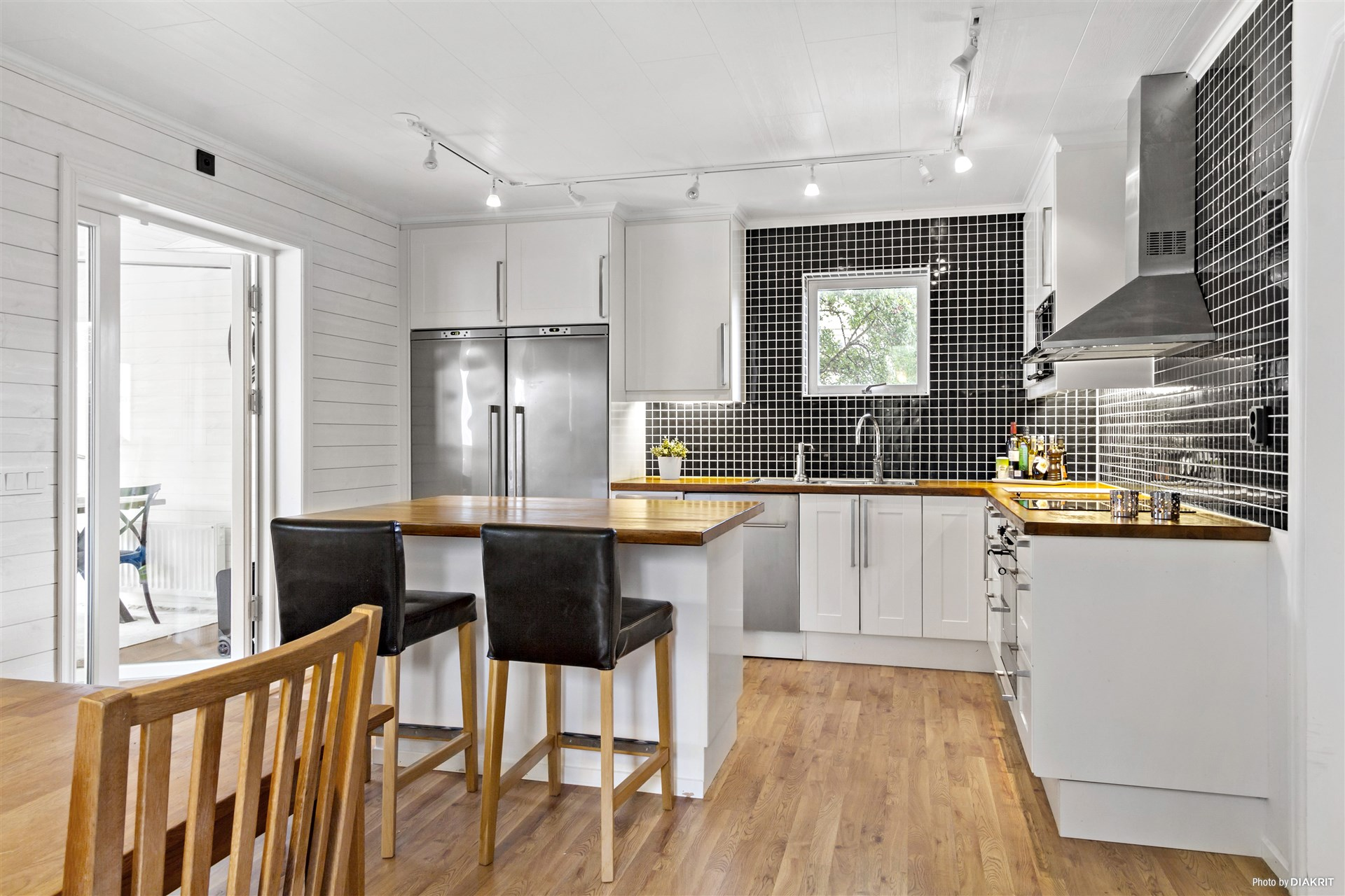 Kök med köksö, matplats och utgång till uterum.