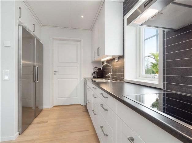 Kök med dörr till tvättstuga/groventré