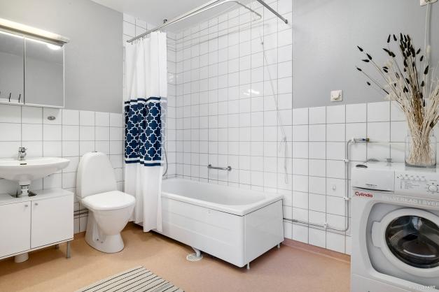 Badrum med badkar och tvättmaskin.