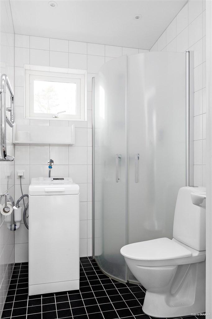 Helkaklat badrum med duschväggar av glas, wc, handfat samt kombinerad tvättmaskin/torktumlare.