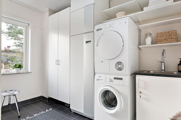 Tvättstuga med klinker på golvet, tvättmaskin och torktumlare av märket Siemens samt tvättvask med diskbänksblandare. Här finns även värmeanläggningen samt elcentral.
