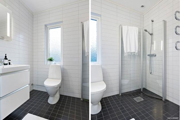 Badrum med helkaklade ljusa väggar och grått klinker på golvet med golvvärme. Stilren inredning i vitt med spegelskåp över tvättställ.