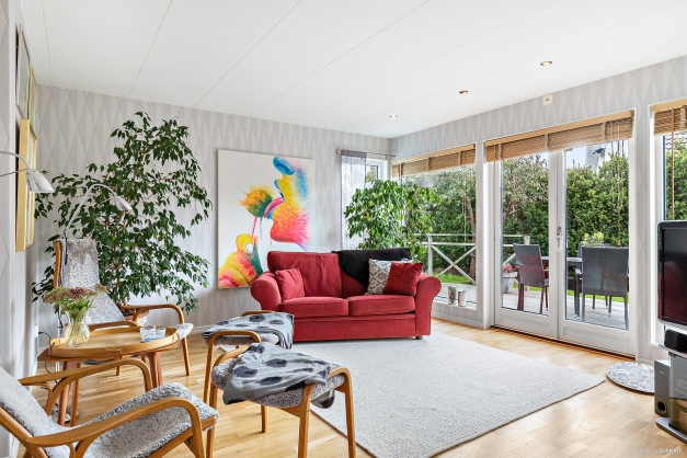Ljust och insynsskyddat vardagsrum med dubbeldörrar ut till altanen!