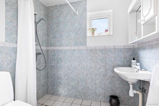 Helkaklat duschrum med fönster.