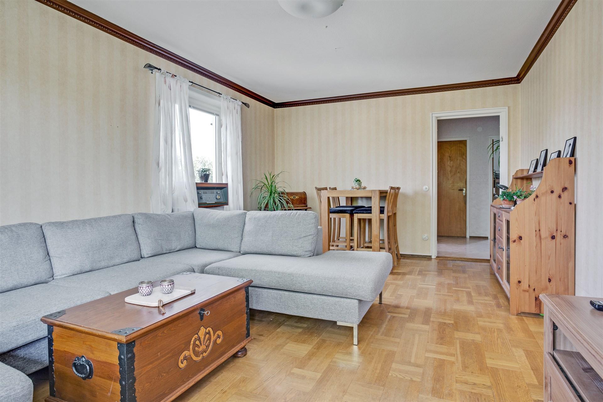 Vardagsrum med fint parkettgolv och fönster åt två håll.