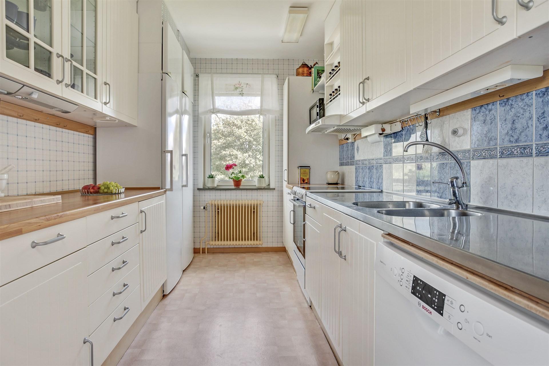 Fräscht kök i vitt med vitrinskåp.