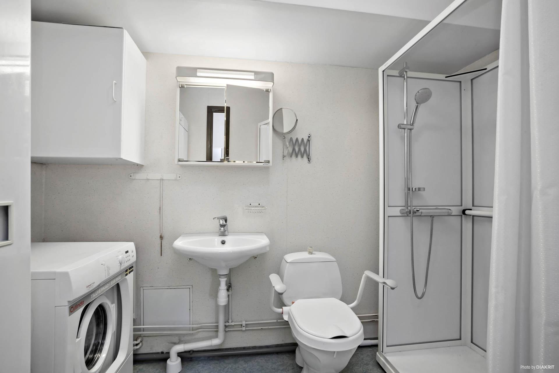Badrum med tvättmaskin och torkskåp