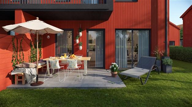 Stensatt uteplats och trädgårdstäppa. Parhusen har svarta fasader och radhus har röda.