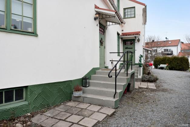 Gjutna trappor med trappräcken i rundsmide resp bandjärn. Mot gården finns tre entrédörrar.