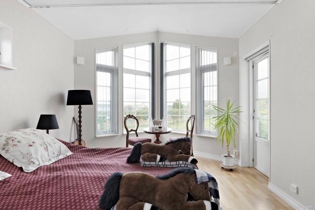 Sovrum 1 med stora vackra fönsterpartier och utgång till uteplats