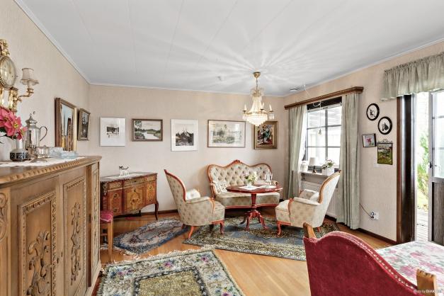 Ljust vardagsrum med parkettgolv och utgång till delvis överbyggt trädäck