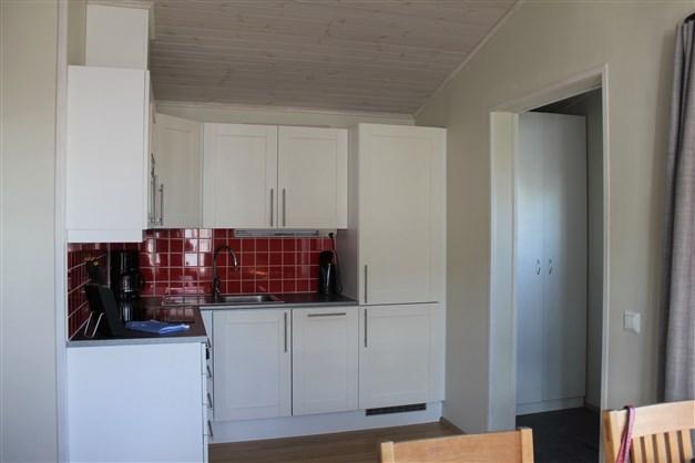 Kök och vardagsrum i öppen planlösning med braskamin